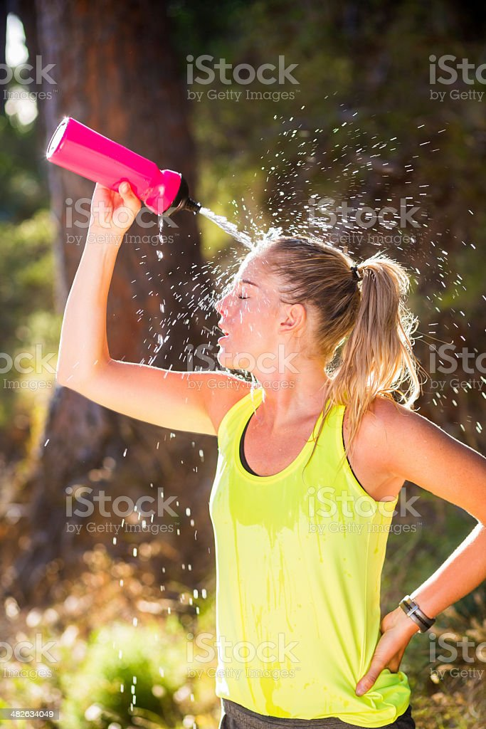 Young woman pouring water over head stock photo