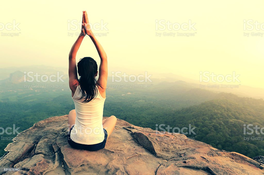 young woman practice yoga at mountain peak cliff stock photo