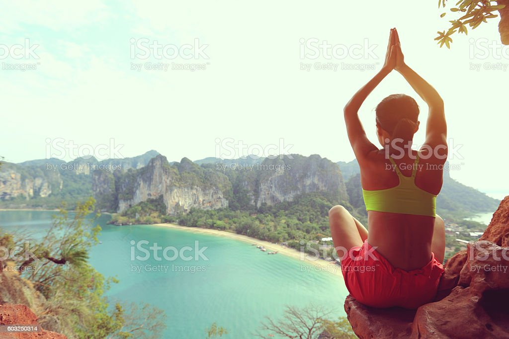 young woman practice yoga on mountain peak cliff stock photo