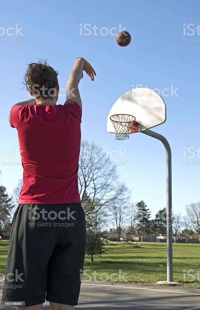 Young woman practicing basketball at park royalty-free stock photo