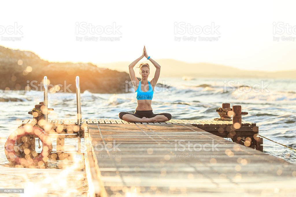 Young woman practicing lotus position on pier stock photo