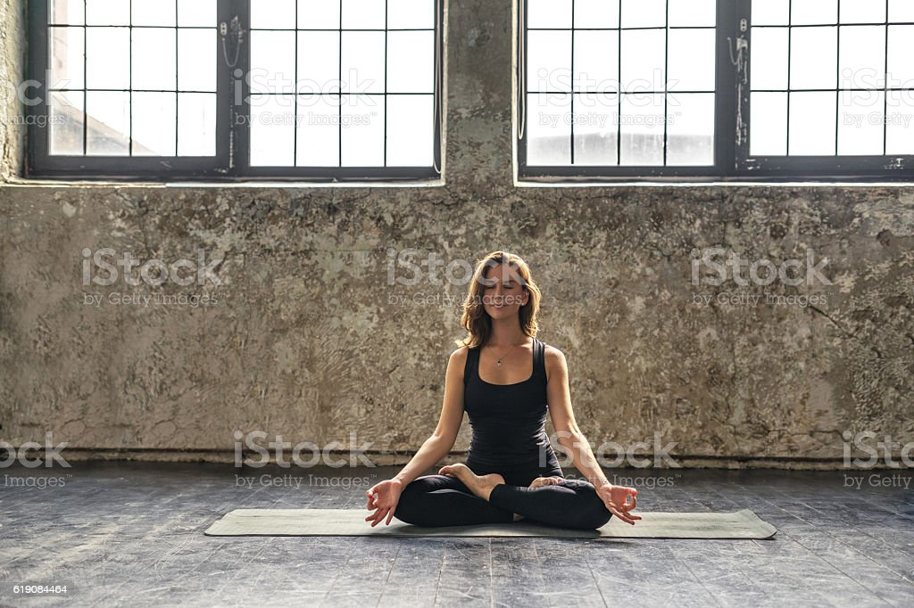 Young woman practicing meditation in a loft studio stock photo