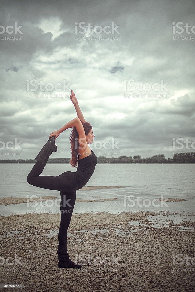Young woman practicing Natarajasana yoga asana in the nature stock photo