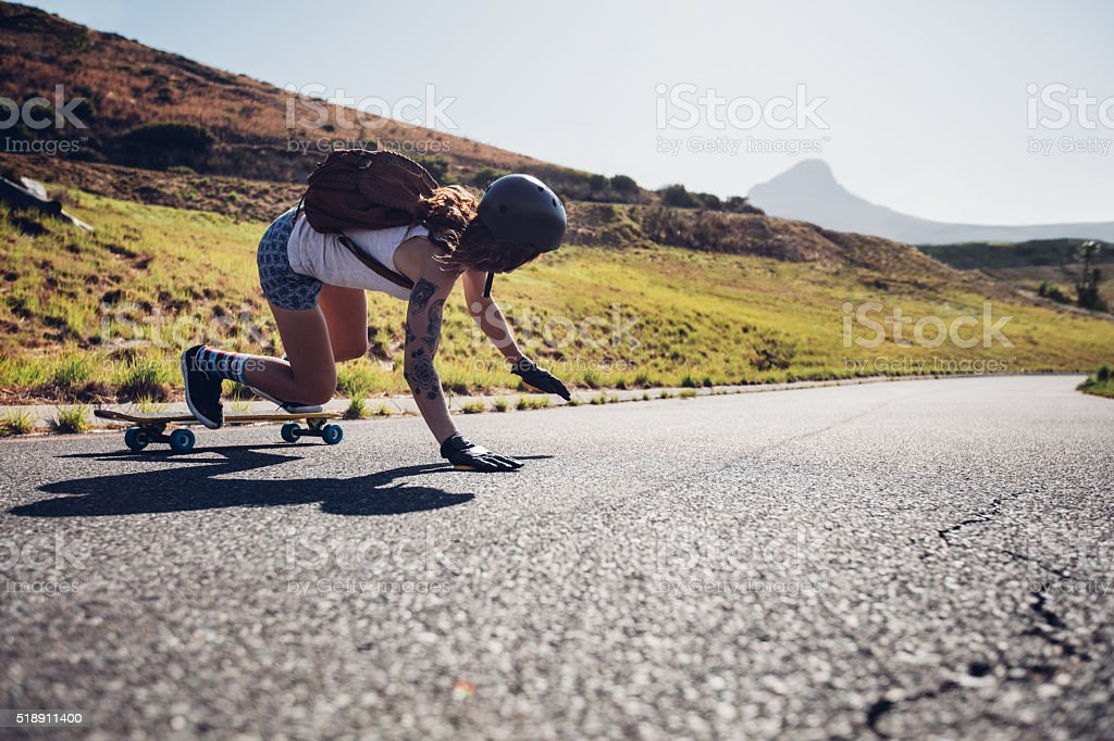 Young woman practicing skateboarding on rural roads stock photo
