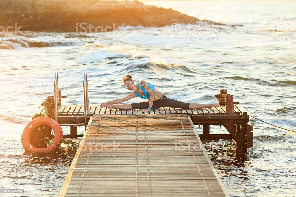 Young woman practicing splits on a pier stock photo