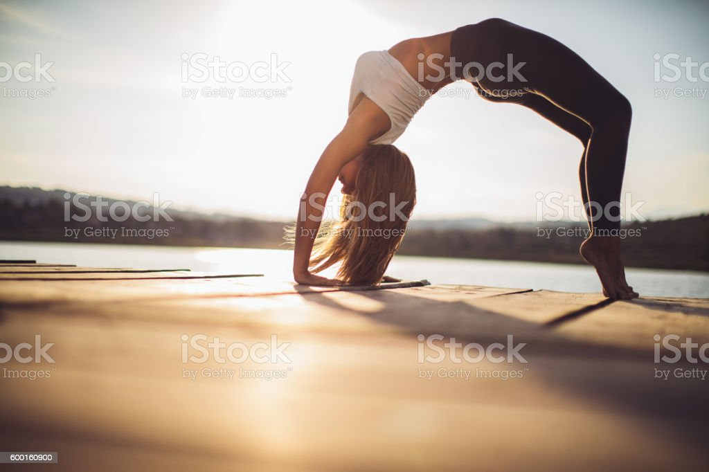 Young woman practicing yoga at lake stock photo