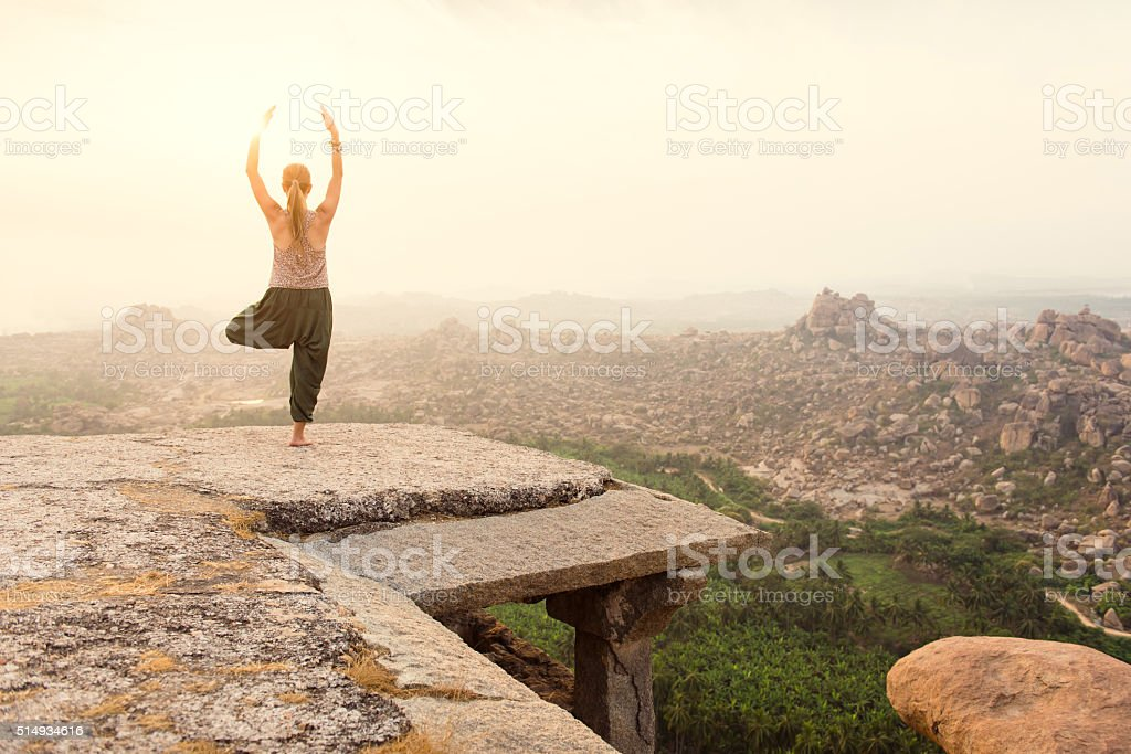 Young woman practicing yoga at mountain cliff on sunrise stock photo