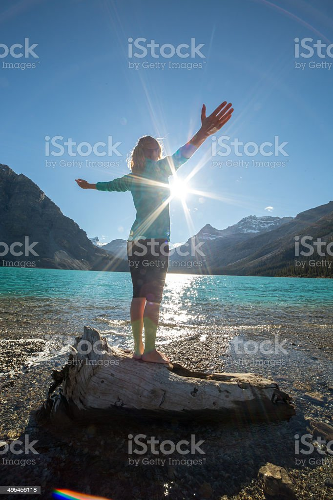 Young woman practicing yoga by the lake at sunrise stock photo