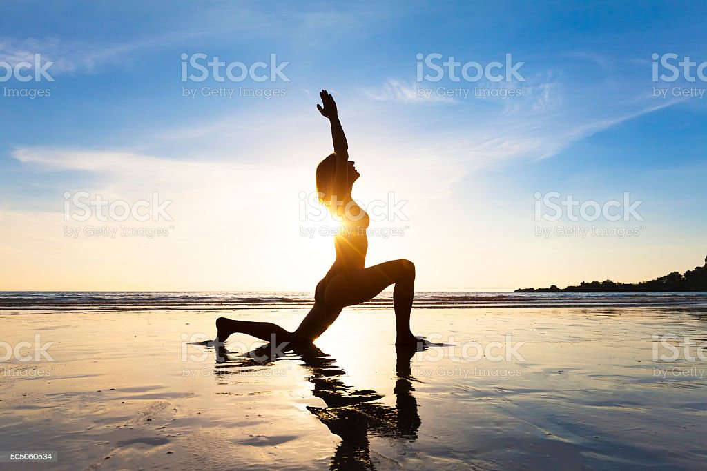Young woman practicing yoga, concept about healthy lifestyle, beach stock photo