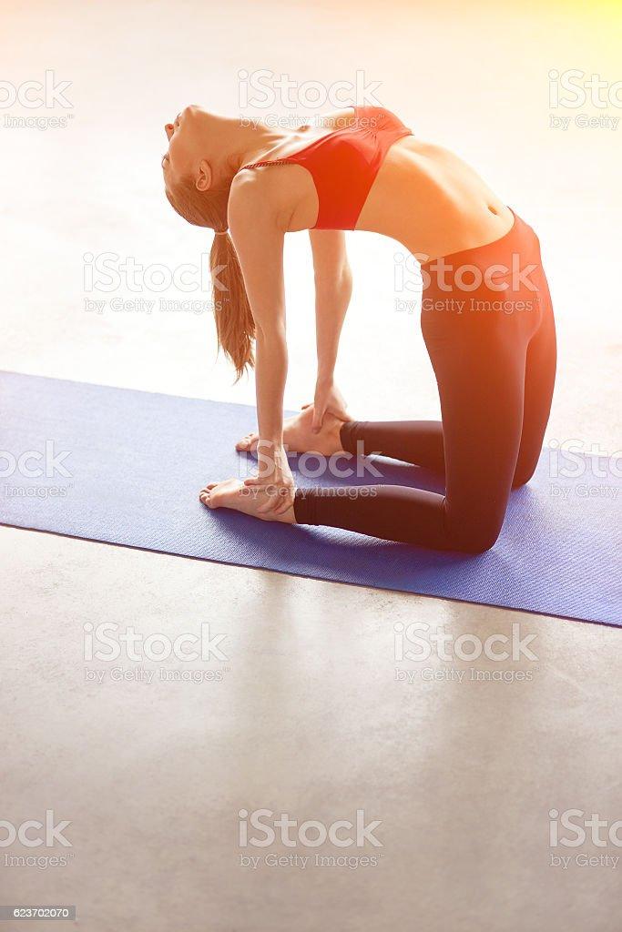 young woman practicing yoga, doing Ushtrasana, Camel Pose stock photo