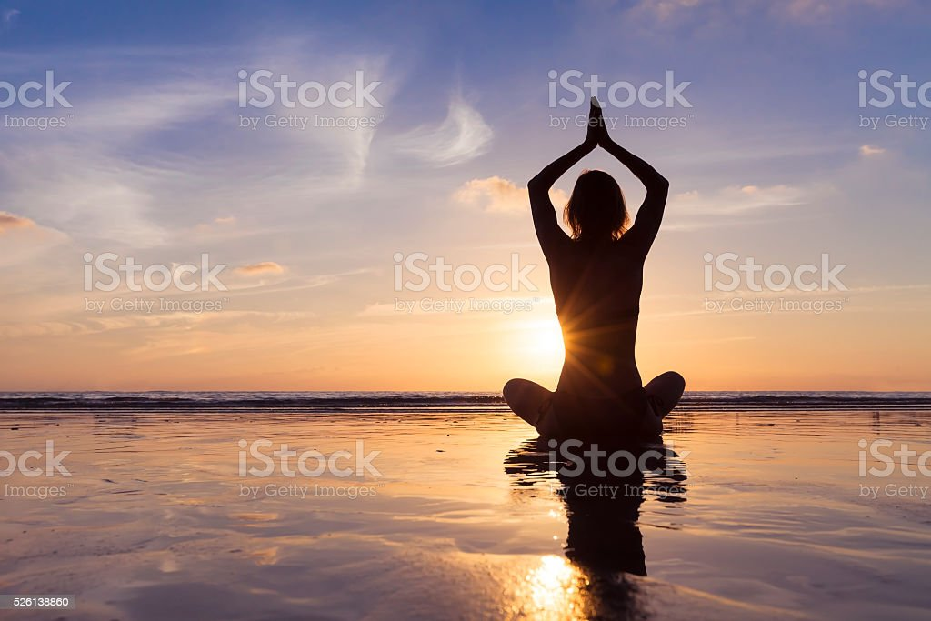 Young woman practicing yoga for meditation and well-being, beach stock photo