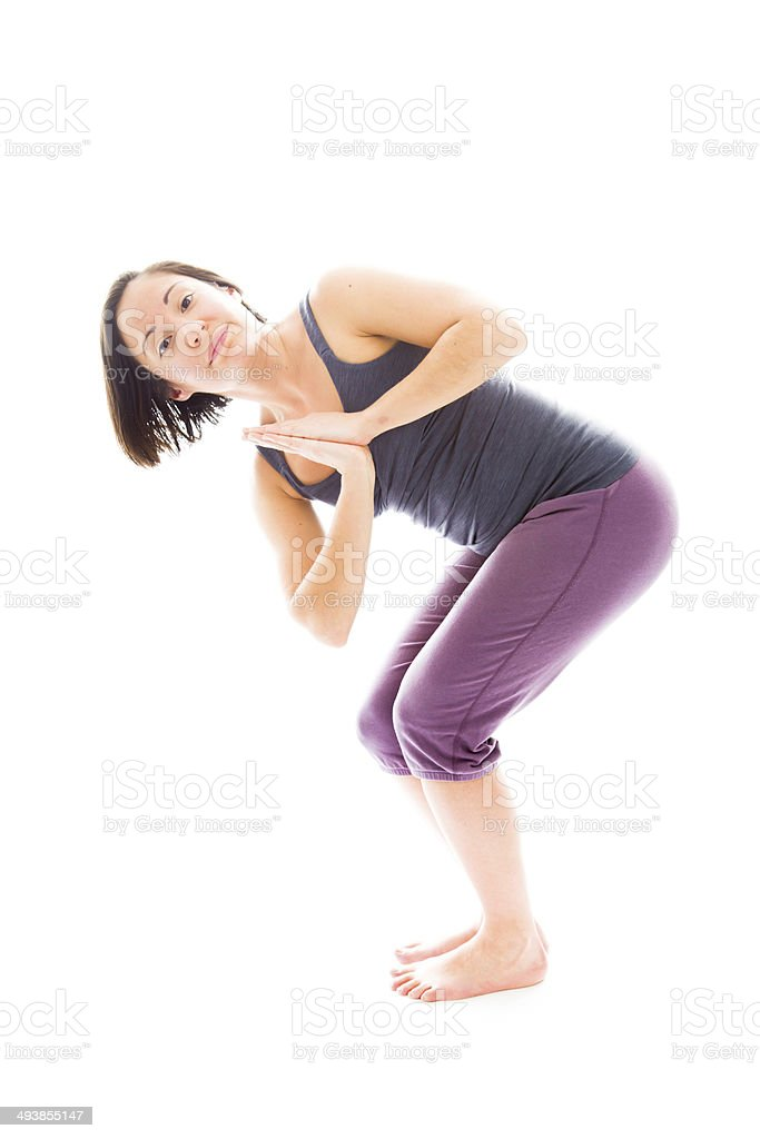 Young woman practicing yoga in chair pose stock photo