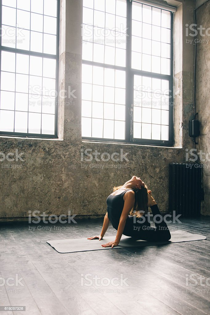 Young woman practicing yoga in urban loft: Cobra Pose (Bhujangasana) stock photo