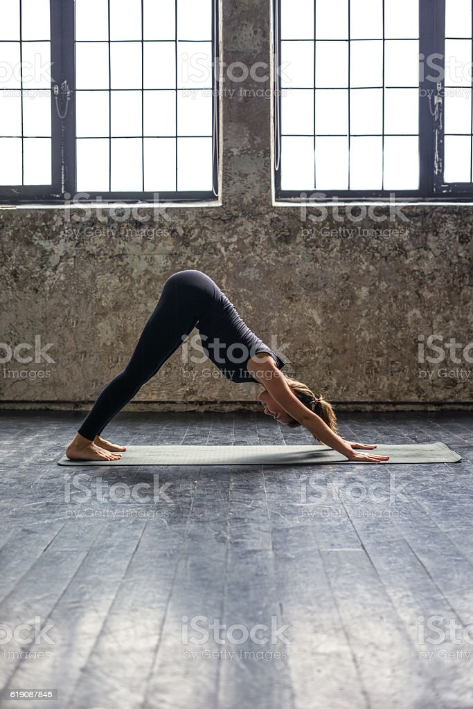 Young woman practicing yoga in urban loft: downward facing dog stock photo