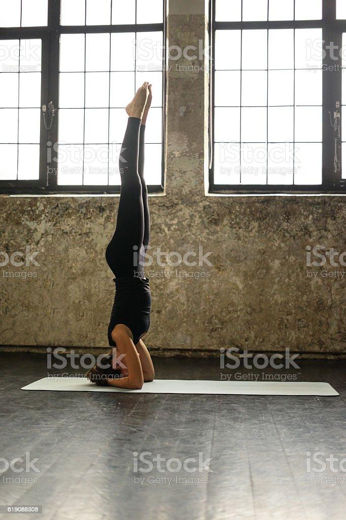 Young woman practicing yoga in urban loft: Salamba Sirsasana pose stock photo