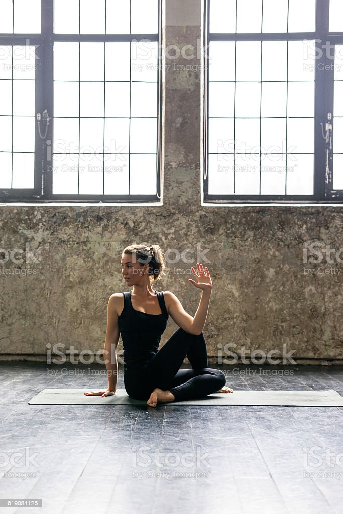 Young woman practicing yoga in urban loft: spinal twist pose stock photo