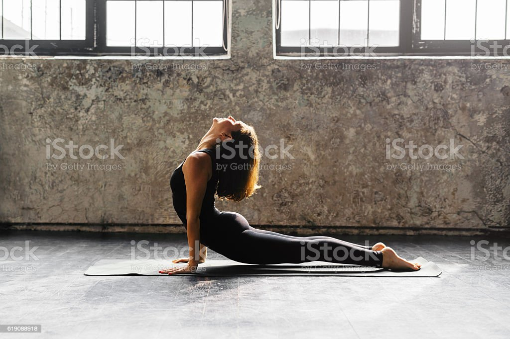 Young woman practicing yoga in urban loft: Upward Facing Dog stock photo