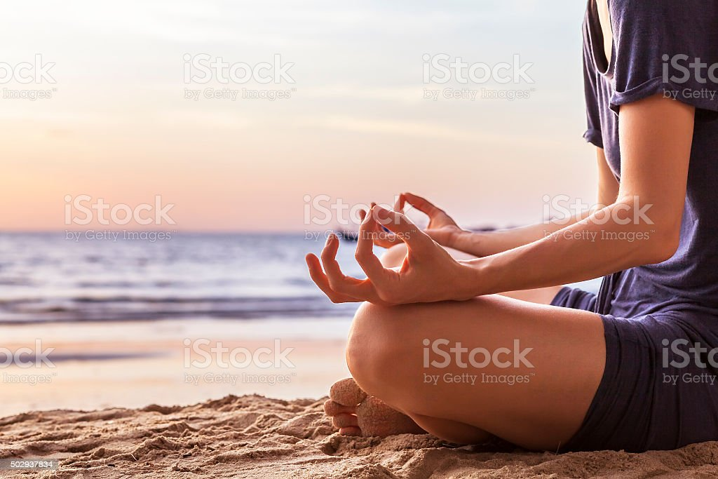Young woman practicing yoga on the beach at sunset stock photo
