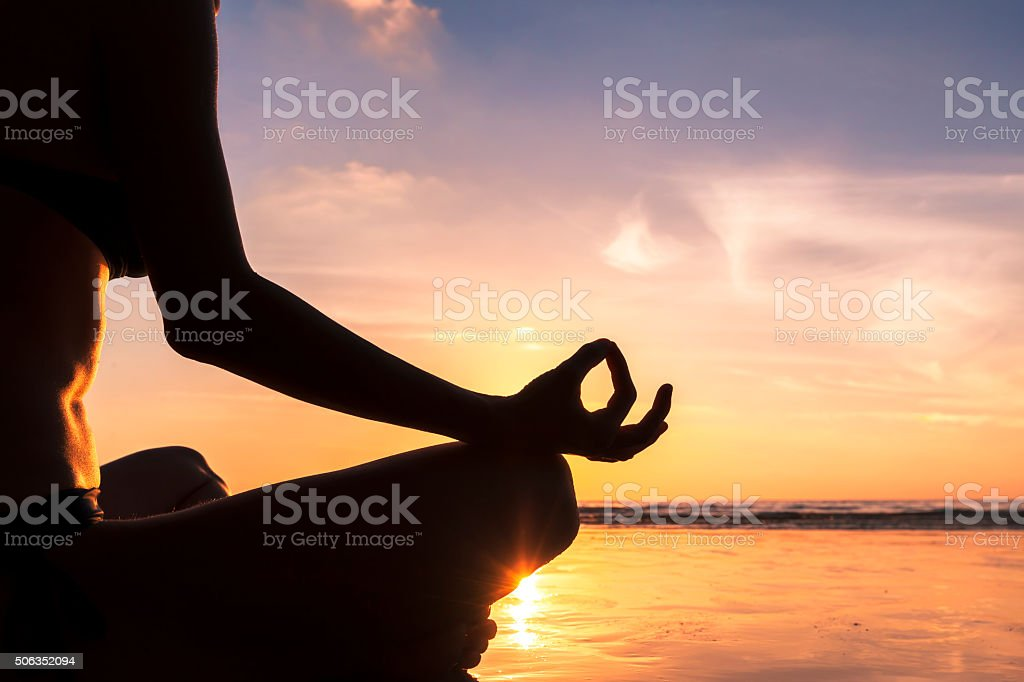 Young woman practicing yoga on the beach, close-up of hand stock photo