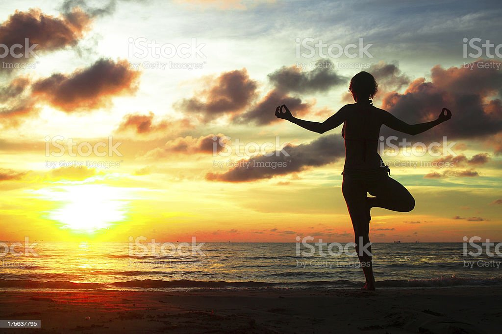 Young woman practicing yoga on the beach during sunset. royalty-free stock photo