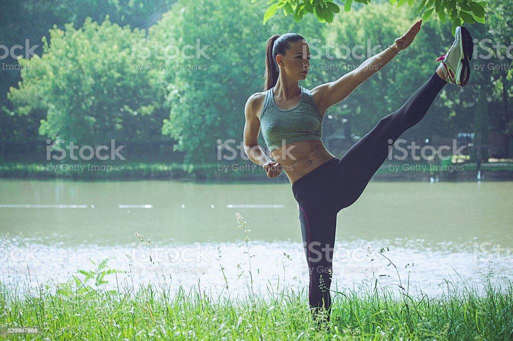 Young woman practising karate balancing on one leg stock photo