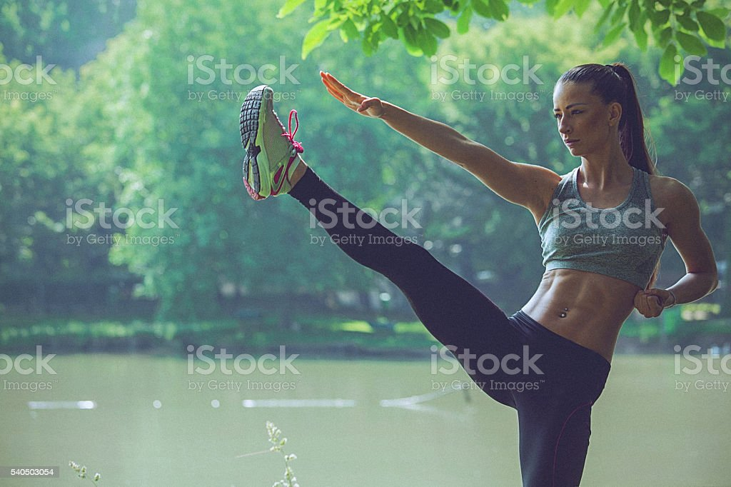 Young woman practising karate balancing on one leg stock photo