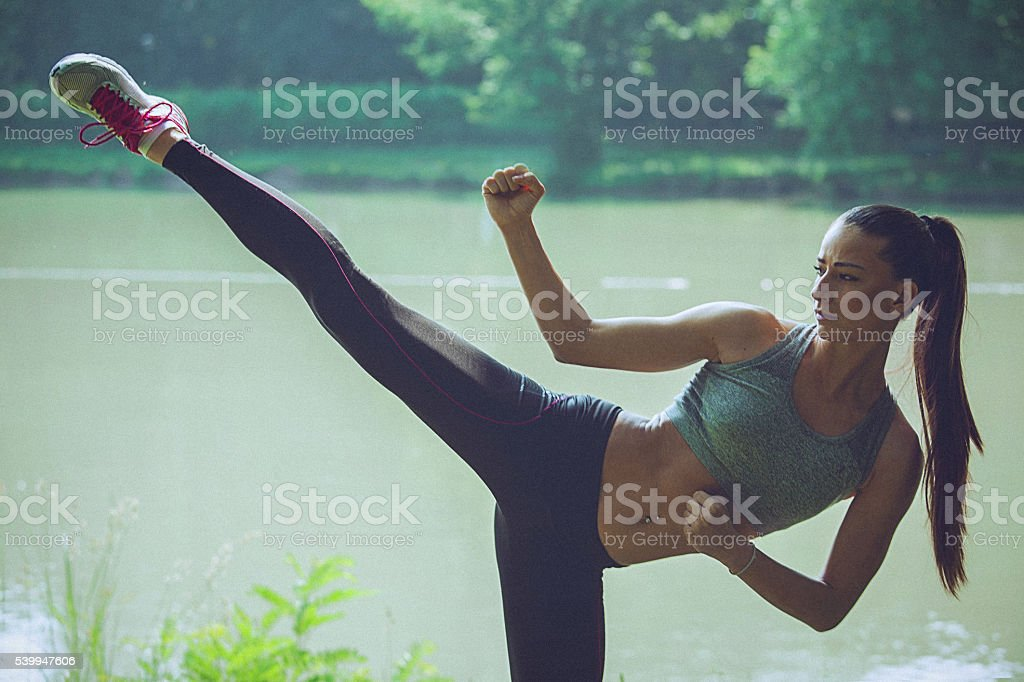 Young woman practising karate on the waterfront stock photo