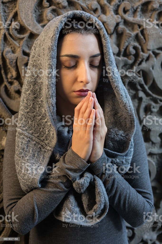Young woman praying in temple stock photo