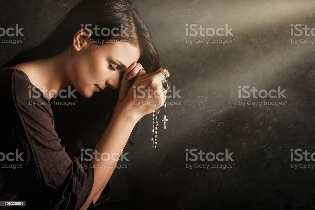 Young woman praying with rosary royalty-free stock photo