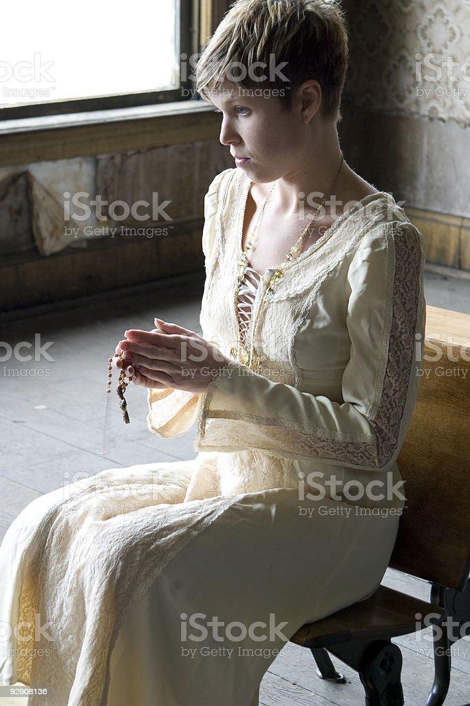 young woman prays in renaissance dress stock photo