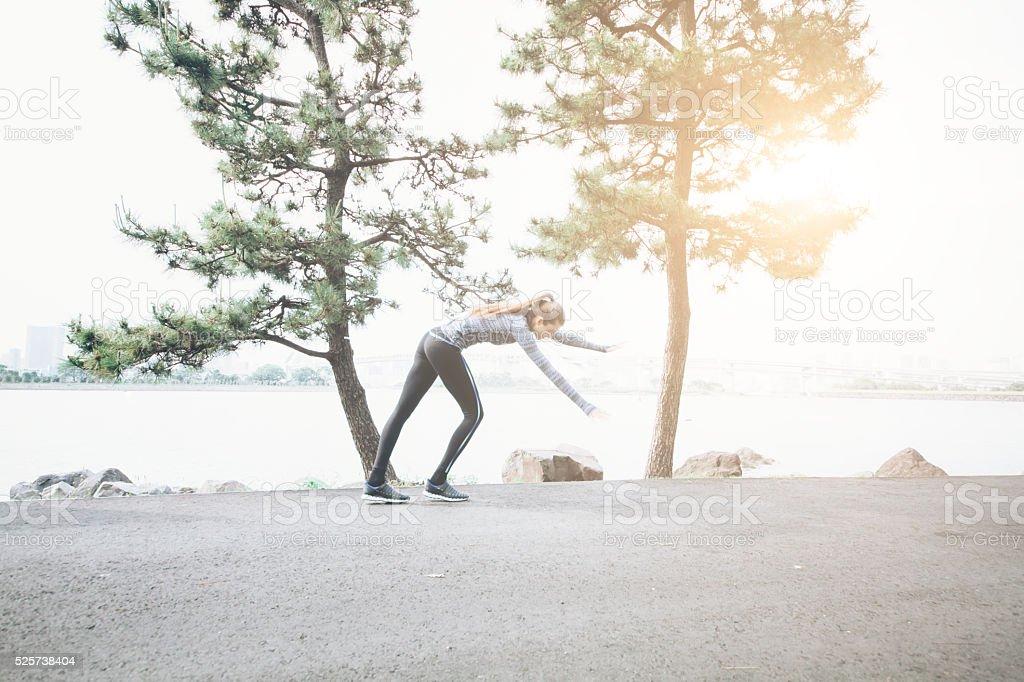 Young woman prepare to make a cartwheel on street stock photo