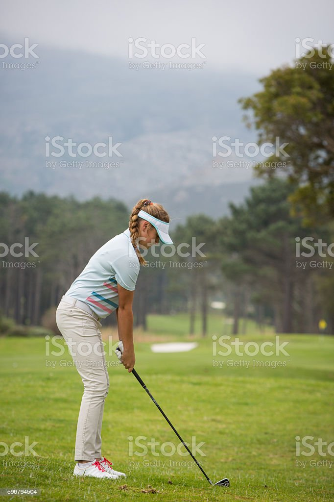 Young woman prepares for her golf shot stock photo