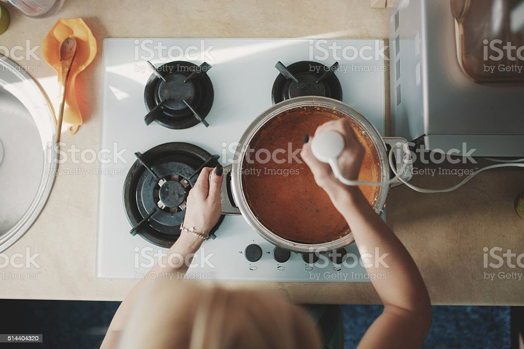 Young woman preparing pumpkin soup stock photo