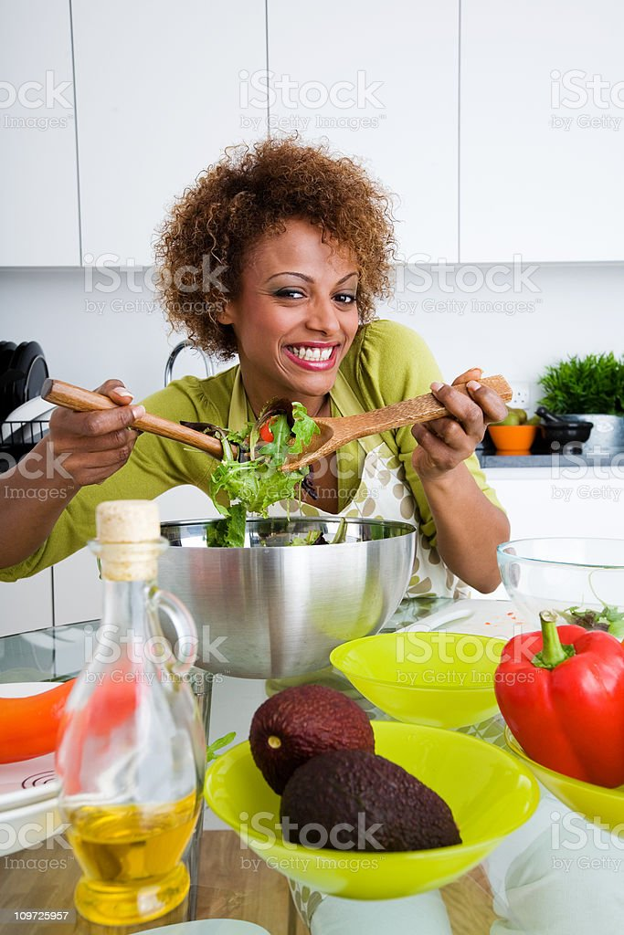 Young Woman Preparing Salad in Kitchen royalty-free stock photo