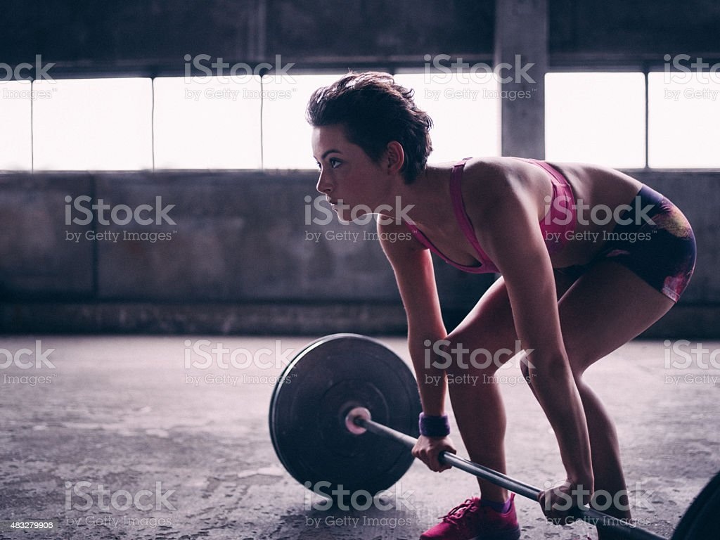 Young woman preparing to lift a barbell with heavy weights stock photo