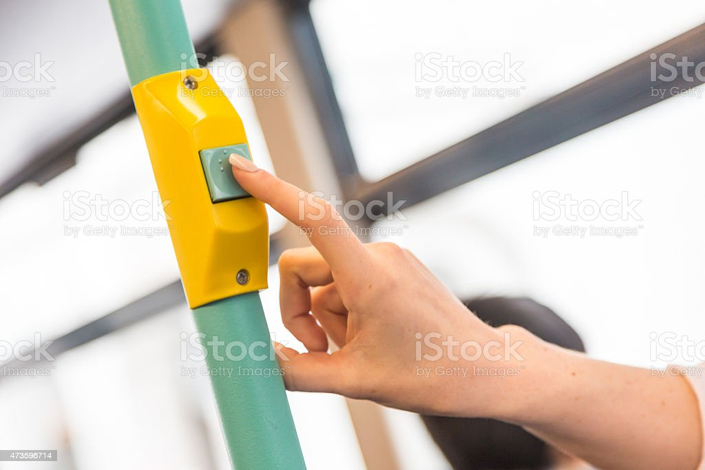 Young woman pressing stop request button on the bus stock photo