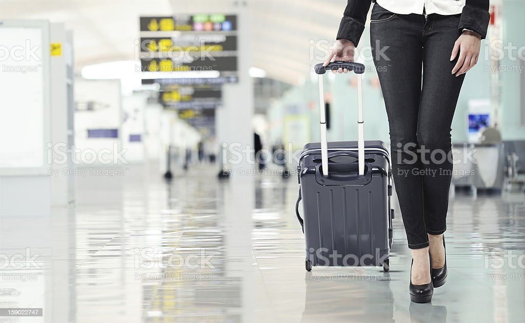 Young woman pulling luggage at the airport stock photo