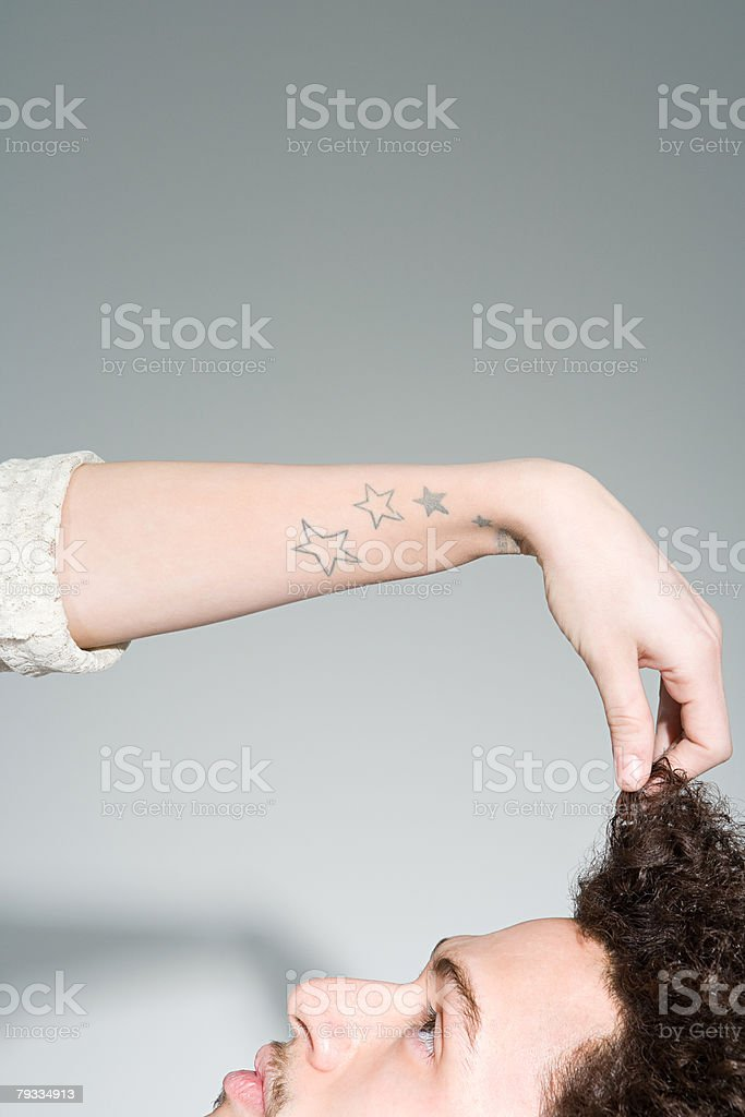 Young woman pulling mans hair stock photo