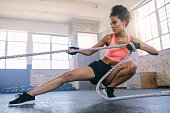 Young woman pulling rope at gym.