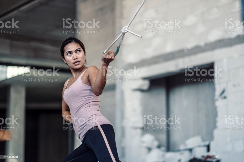 Young woman pulling weights in improvised ghetto fitness stock photo