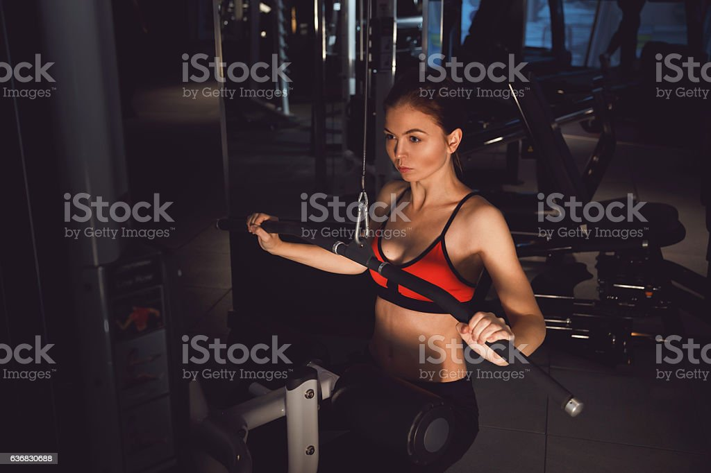 Young woman pulls on the training appliance for the arms stock photo