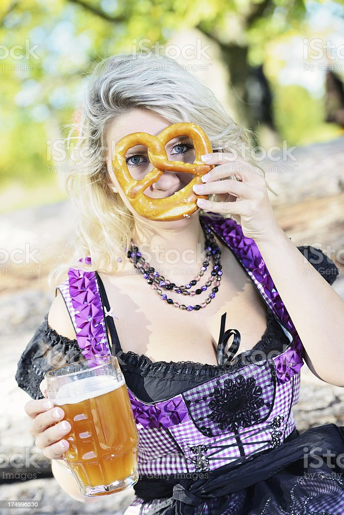 Young Woman Purple Dirndl Dress with Beer and Prezel stock photo