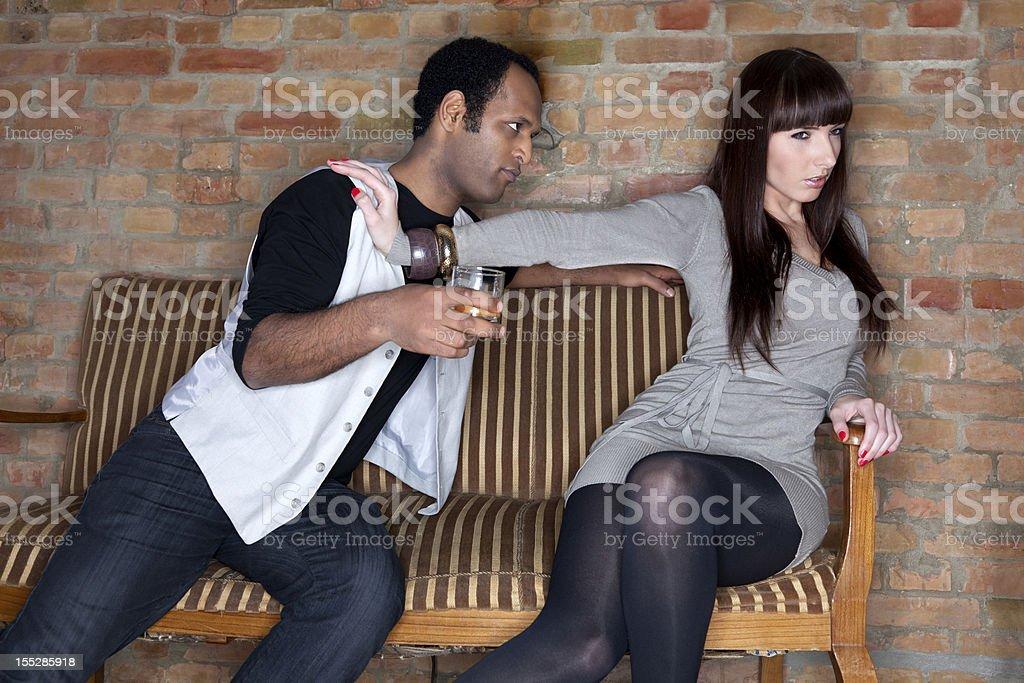 Young Woman Pushing Away a Drunk Man. stock photo