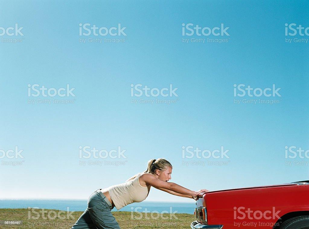 Young woman pushing car stock photo