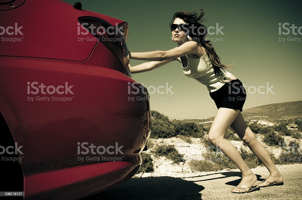 Young Woman Pushing Red Car Along Road in Desert stock photo