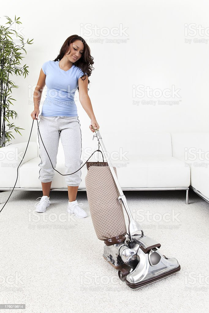 Young Woman Pushing Vacuum Cleaner stock photo