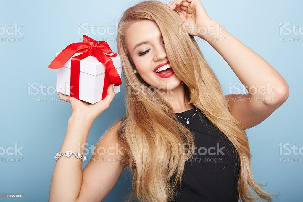 Young woman puts her ear to the present wrapped. stock photo