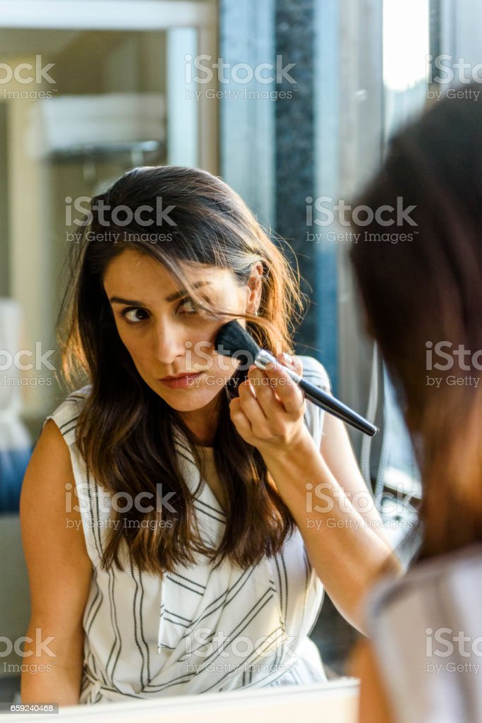 Young woman puts on her make up in the bathroom of her hotel room stock photo