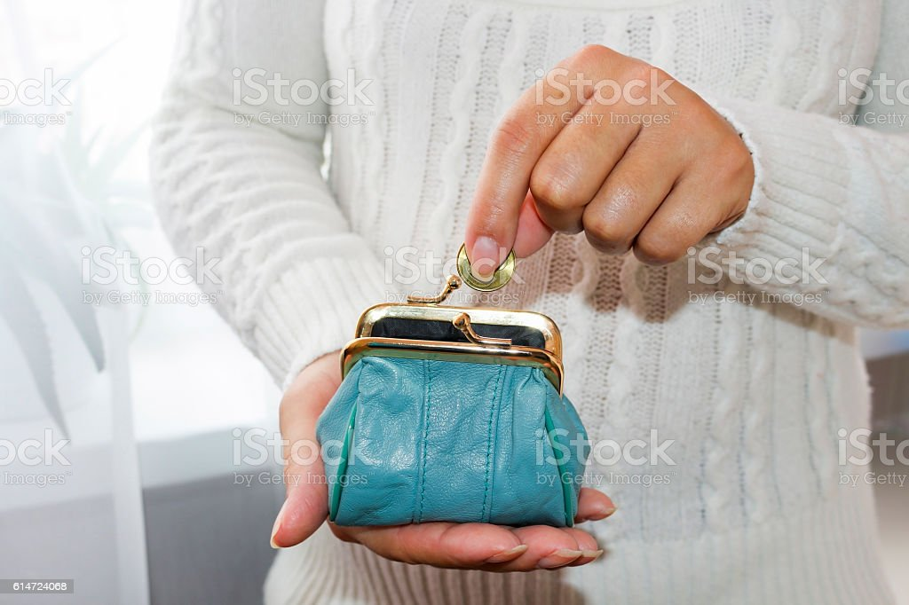 Young woman putting coin in purse. Leather purse for coins. stock photo