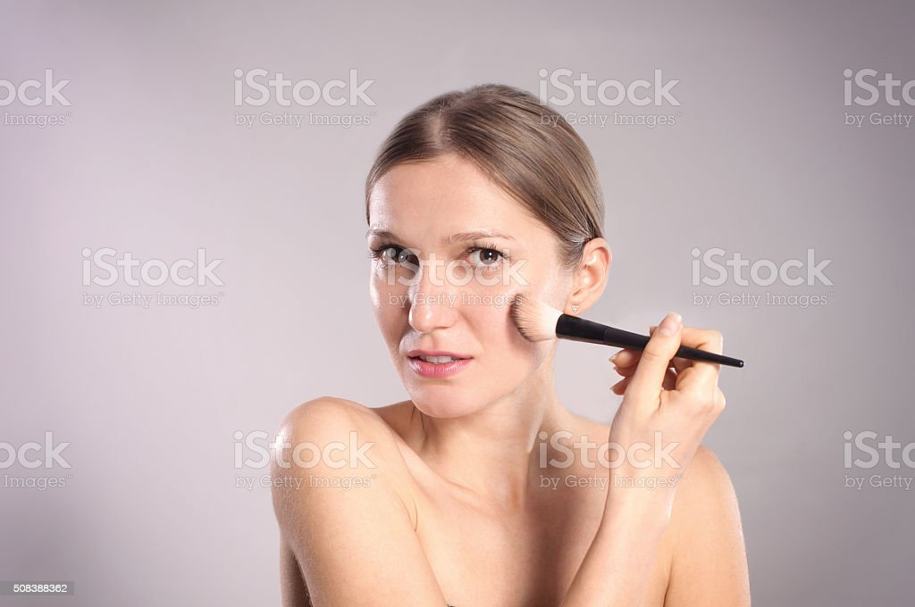 Young woman putting make-up stock photo